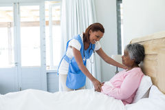 Female doctor comforting senior woman on bed Royalty Free Stock Photos