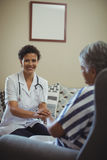 Female doctor comforting senior woman in living room Stock Photography