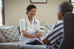Female doctor comforting senior woman in living room Stock Photos