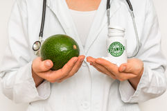 Female doctor compare pile of pills with fresh avocado Royalty Free Stock Photos