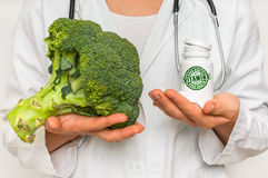 Female doctor compare pile of pills with fresh broccoli Stock Image