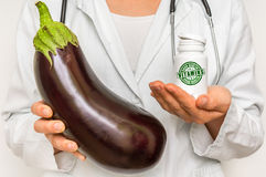 Female doctor compare pile of pills with fresh eggplant Stock Photography