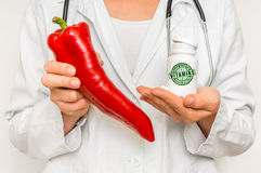 Female doctor compare pile of pills with fresh red pepper Royalty Free Stock Image