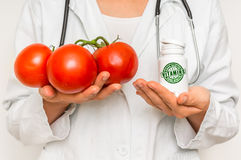 Female doctor compare pile of pills with fresh tomatoes Stock Photo