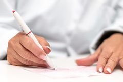 Female doctor completing a medical prescription or doctor`s orders, closeup stock images