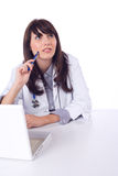 Female doctor on computer at desk Stock Photography