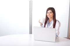 Female doctor on computer at desk Stock Image