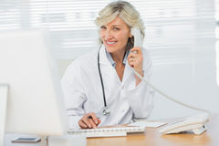 Female doctor with computer using phone at medical office Stock Photos