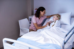 Female doctor consoling patient during visit in ward Stock Photography