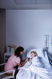 Female doctor consoling patient during visit in ward Stock Images