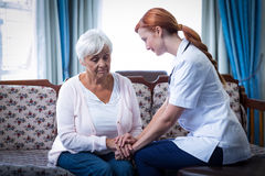 Female doctor consoling senior woman in living room Stock Photos