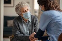Free Female Doctor Consoling Senior Woman Wearing Face Mask During Home Visit Royalty Free Stock Images - 201515079