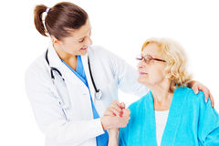 Female Doctor Consoling Senior Woman Stock Photo
