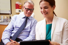 Female Doctor In Consultation With Male Patient. Using Digital Tablet Smiling stock photo