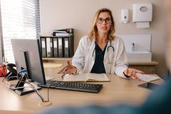 Female doctor consulting a patient in clinic stock photo