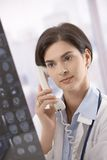 Female doctor consulting on phone Royalty Free Stock Images