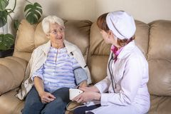 Female doctor consulting with senior patient stock image
