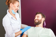 Female doctor dentist smiling to her patient stock image