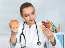 Female doctor or dietologist holds packs of pills and an apple Stock Images
