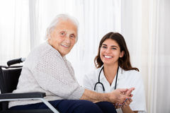 Female Doctor With Disabled Senior Patient In Hospital Royalty Free Stock Photos