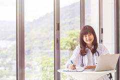 Female doctor discussing with her male patient beside the window royalty free stock photography