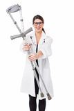 Female doctor displaying a set of crutches Royalty Free Stock Images