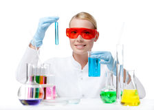 Female doctor does some experiments. Female doctor in spectacles does some experiments with blue liquid, isolated on white stock photos