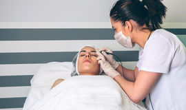Female doctor doing getting rf lifting to woman in clinic Royalty Free Stock Photos