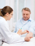 Female doctor doing injection to old man Stock Photo