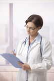 Female doctor doing paperwork in hospital Stock Photos