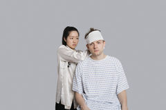 Female doctor dressing patient's head with bandage Stock Image