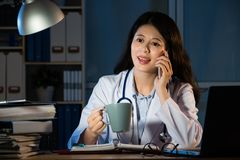 Female doctor drinking coffee and making call Stock Images