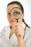 Female doctor examination. Female doctor scrutiny with a magnifying glass Stock Photography