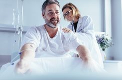 Mature man sitting in hospital bed and physician doing checkup. Female doctor examine patient`s back. Mature men sitting in hospital bed and physician doing Stock Images