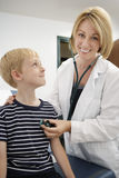 Female Doctor Examining Boy. Portrait of a happy female doctor examining boy royalty free stock photos