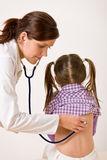 Female doctor examining child with stethoscope Stock Photo