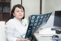 Female doctor examining an CT scanner results Stock Photography