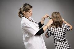 Female doctor examining ear Royalty Free Stock Image