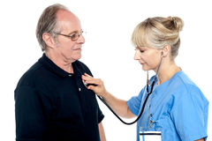 Female doctor examining an elderly man Royalty Free Stock Image