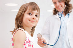 Female doctor examining happy child Royalty Free Stock Photos