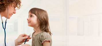 Female doctor examining little girl. Room for text Royalty Free Stock Images