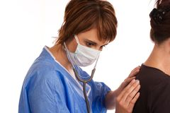 Female doctor examining a patient. Young Caucasian female doctor listening to a patient's lungs using a stethoscope Royalty Free Stock Photography