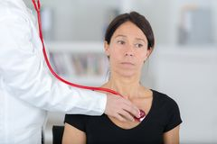 Female doctor examining patient with stethoscope stock photo