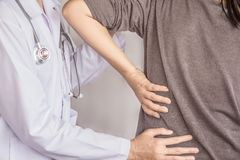 Female doctor examining a patient suffering from back pain royalty free stock image