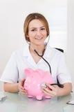 Female Doctor Examining Piggybank Royalty Free Stock Photo