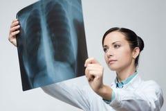 Female doctor examining x-ray image. Confident female doctor examining accurately a rib cage x-ray stock image