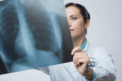 Female doctor examining x-ray image. Confident female doctor examining accurately a rib cage x-ray royalty free stock image