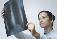 Female doctor examining x-ray image. Confident female doctor examining accurately a rib cage x-ray royalty free stock photo