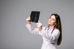 Female doctor examining an x-ray image. Focus is on the x-ray image isolated on grey background. Royalty Free Stock Photo