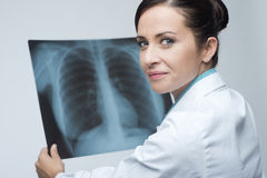 Female doctor examining x-ray image. Smiling attractive female doctor checking a rib cage x-ray image stock photos